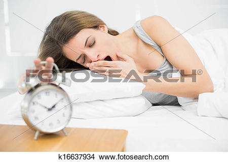 Clipart woman turning off alarm jpg royalty free download Stock Photo of Tired brunette woman turning off the alarm clock ... jpg royalty free download