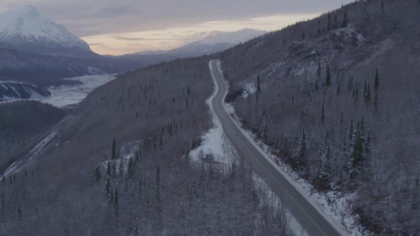 Twiligh highway clipart graphic freeuse 4K aerial video follow Glenn Highway, snow covered, wooded hills, Sutton,  Alaska, twilight graphic freeuse