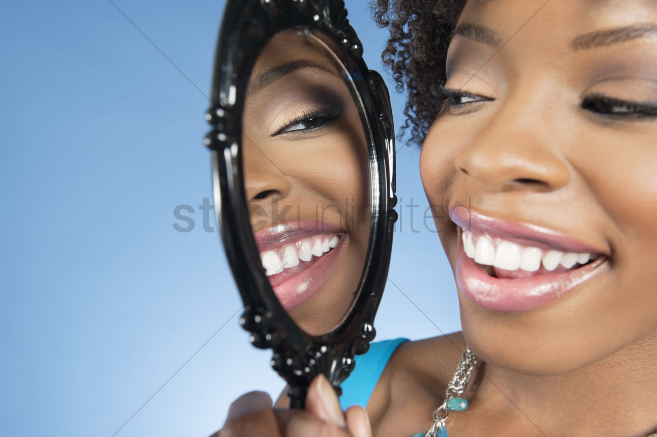 Women looking at herself in the mirror clipart clip freeuse Close-up of a young woman looking at herself in mirror and ... clip freeuse